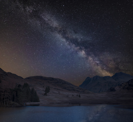 Digital composite image of Milky Way over stunning landscape image of Blea Tarn in UK Lake District Standard-Bild