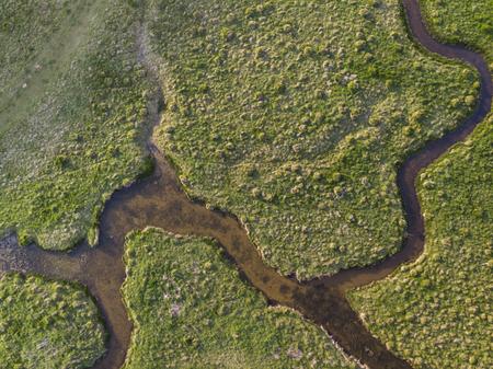 Piękny obraz krajobrazu drona z lotu ptaka meandrującej rzeki przez bagna o wschodzie słońca Zdjęcie Seryjne