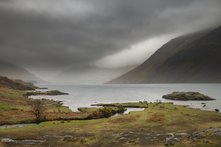 Beautiful long exposure landscape image of Wast Water in UK Lake District during moody Spring evening