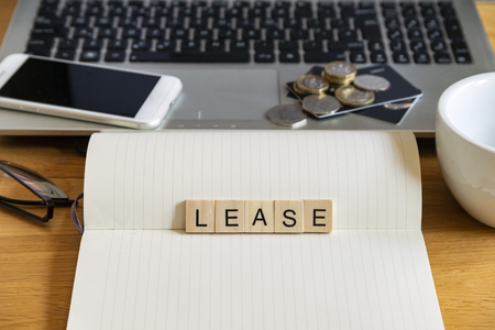 Conceptual keyword lease in generic wooden tile letters  in personal home desk setting with laptop, notebook and accessories Stock Photo