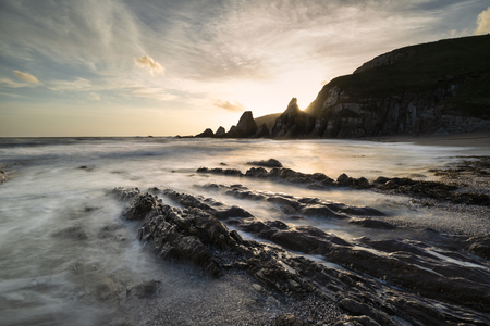 Beautiful sunset landscape image of Westcombe Beach in Devon England with jagged rocks on beach and stunning cloud formations
