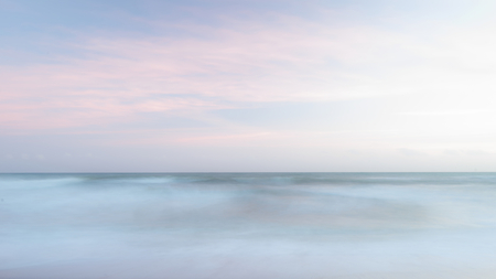 Beautiful colorful landscape image of blurred waves at sunset in Devon Enlgand