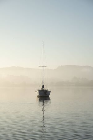 Beautiful unplugged landscape image of sailing yacht sitting still in calm lake water in Lake District during peaceful misty Autumn Fall sunrise 免版税图像