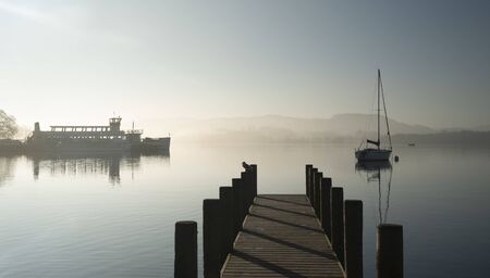 Beautiful unplugged landscape image of sailing yacht sitting still in calm lake water in Lake District during peaceful misty Autumn Fall sunrise