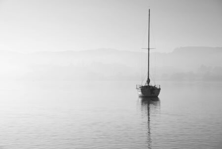 Beautiful unplugged landscape image of sailing yacht sitting still in calm lake water in Lake District during peaceful misty Autumn Fall sunrise Imagens