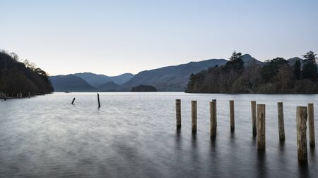Beautiful long exposure landscape image of Derwent Water in Lake District during Autumn Fall sunrise with soft pastel colors
