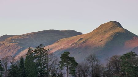 Landscape image of Catbells in Lake District hit by first light during Autumn Fall sunrise viewed from Derwent Water at Keswick