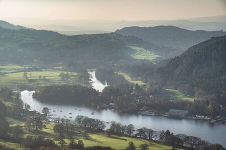 Beautiful Autumn Fall landscape image of view from Gummers How down onto Derwent Wter in Lake District