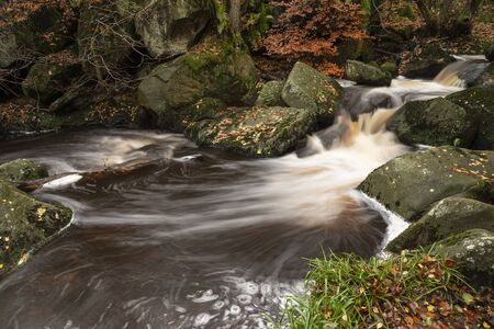 Beautiful close up of stream flowing over rocks in Autumn Fall forest landscape in Peak District in England Фото со стока