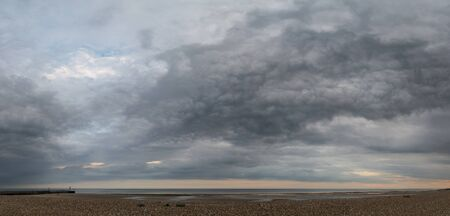 Beautiful panorama landscape image of beach at low tide with moody storm clouds gathering overhead