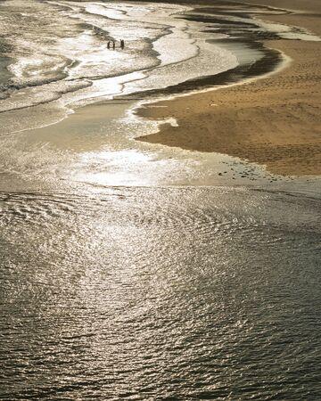 Persone non identificate che giocano nell'oceano a Three Cliffs Bay nel Galles del Sud in una sera d'estate Archivio Fotografico