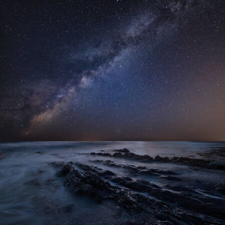 Beautiful composite landscape image of Mily Way core over sea rocks and cliffs with long exposure tide on beach
