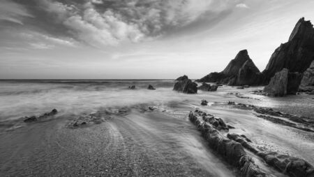 Beautiful black and white sunset landscape image of Westcombe Beach in Devon England