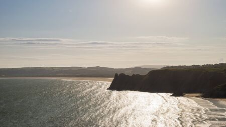 Beautiful Summer evening sunset beach landscape image at Three Cliffs Bay in South Wales