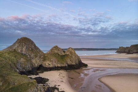 Beautiful drone landscape image of Three Cliffs Bay in South Wales during Summer sunrise