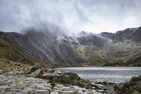 Stunning dramatic Winter landscape image of Llyn Idwal and snowcapped Glyders Mountain Range in Snowdonia