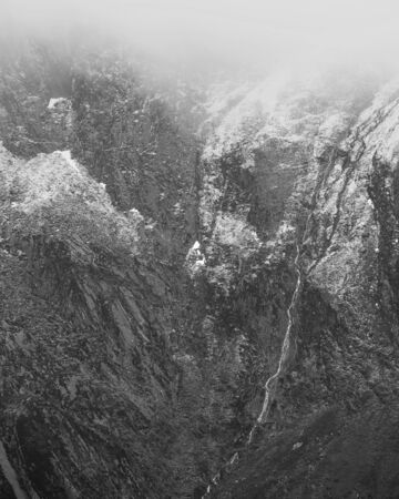 Stunning dramatic landscape image of snowcapped Glyders mountain range in Snowdonia during Winter in black and white