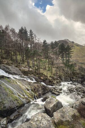 Beautiful landscape image of Ogwen Valley river and waterfalls during Winter with snowcapped mountains in background