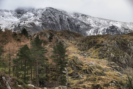 Stunning dramatic landscape images of Ogwen Valley in Snowdonia during Winter with snowcapped Glyers mountain range in the background