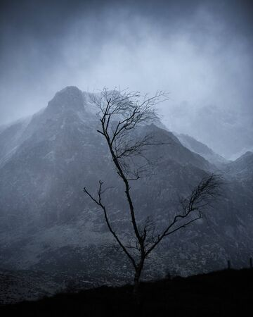 Stunning moody dramatic Winter landscape mountain image of snowcapped Y Garn in Snowdonia