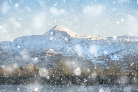 Beautiful Winter landscape image of Mount Snowdon and other peaks in Snowdonia National Park in heavy snow storm