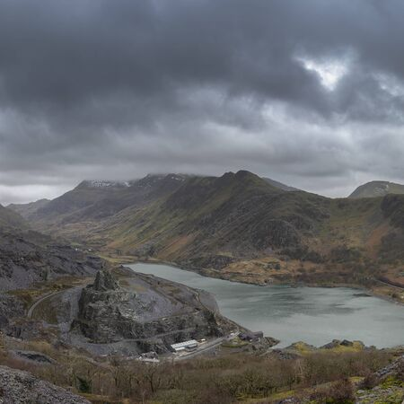 Stunning landscape image of Dinorwig Slate Mine and snowcapped Snowdon mountain in background during Winter in Snowdonia with Llyn Peris in foreground