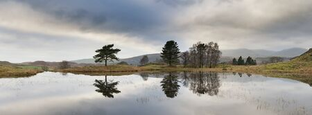 Beautiful landscape image of moody storm clouds over Kelly Hall Tarn in Lake District during late Autumn Fall afternoon