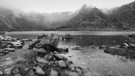 Stunning dramatic Winter landscape image of Llyn Idwal and snowcapped Glyders Mountain Range in Snowdonia in black and white
