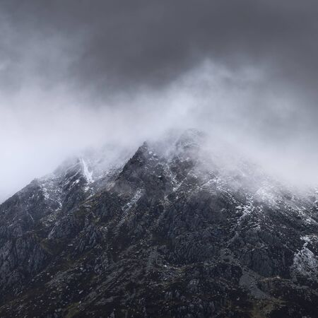 Stunning detail landscape images of snowcapped Pen Yr Ole Wen mountain in Snowdonia during dramatic Winter storm Stok Fotoğraf