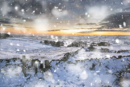 Winter sky over snow covered Winter landscape in Peak District at sunset in heavy snow storm Imagens
