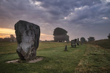 Beautiful Summer sunrise landscape of Neolithic standing stones in English countryside with gorgeous light with background mist
