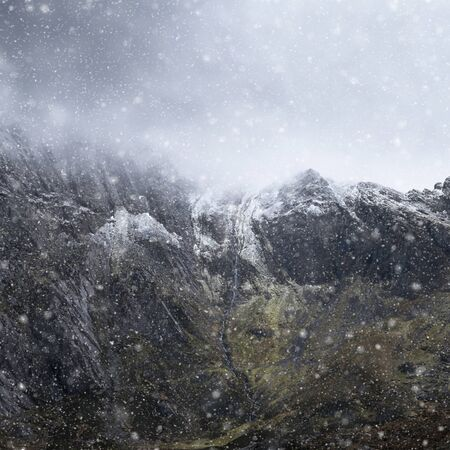 Stunning dramatic landscape image of snowcapped Glyders mountain range in Snowdonia during Winter with menacing low clouds hanging at the mountain peaks