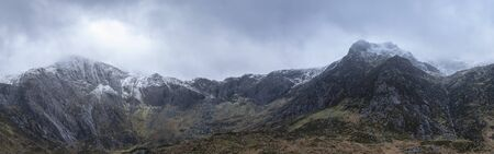 Stunning dramatic panorama landscape image of snowcapped Glyders mountain range in Snowdonia during Winter with menacing low cloudshanging at the mountain peaks