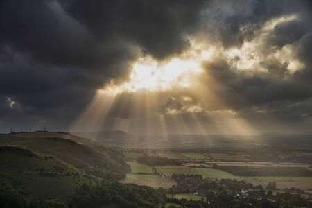 Beautiful Summer landscape image of escarpment with dramatic storm clouds and sun beams streaming down Stockfoto