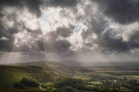 Beautiful Summer landscape image of escarpment with dramatic storm clouds and sun beams streaming down Archivio Fotografico