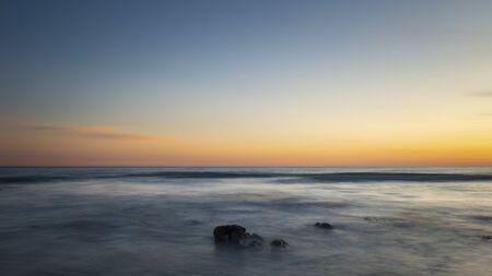 Beautiful Summer landscape sunset image of colorful sky over calm long exposure sea