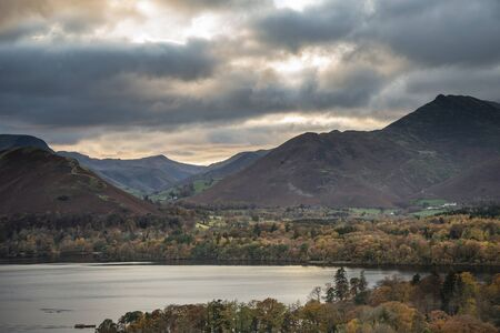 Beautiful Autumn Fall landscape image of view from Castlehead in Lake District over Derwentwater towards Catbells and Grisedale Pike at sunset with epic lighting in sky
