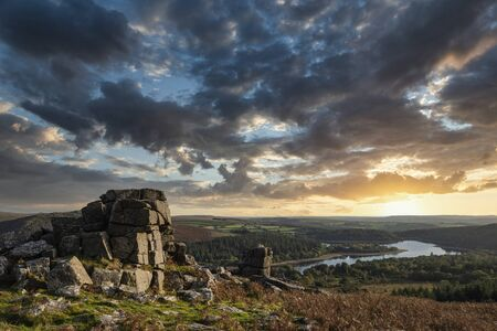 Epic sunset over landscape of Leather Tor in Dartmoor during Summer with dramatic sky Фото со стока
