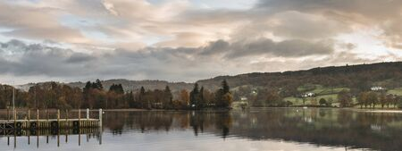 Beautiful sunrise landscape over Coniston Water during Autumn with mist and wispy clouds