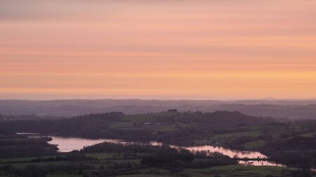 Stunning Peak District Winter landscape of view from top of Hen Cloud over countryside and towards Tittesworth Reservoir