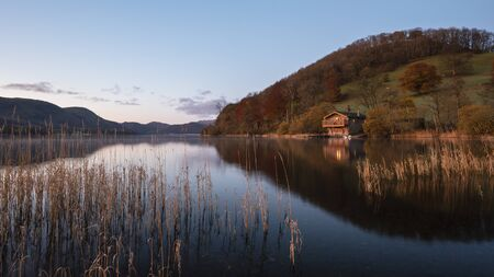 Stunning sunrise Autumn Fall landscape image of Ullswater in Lake District with golden sunlight
