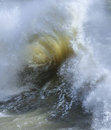 Stunning image of individual wave breaking and cresting during violent windy storm with superb wave detail