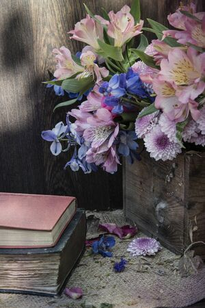 Beautiful vintage look applied to romantic flower and garden paraphenalia still life image with Spring and Summer seasonal blooms