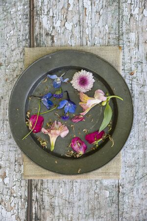 Flat lay top down view image of romantic vintage look of flower petals still life on rustic old worn background