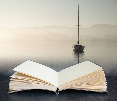 Digital composite concept image of open book wth Beautiful unplugged landscape image of sailing yacht sitting still in calm lake water in Lake District during peaceful misty Autumn Fall sunrise
