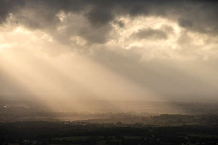 Stunning landscape image of sunset over English countryside with sun beams lighting up the fields below