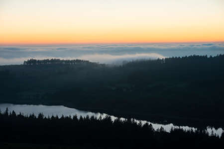 Epic landscape image of cloud inversion at sunset over Dartmoor National Park in Engand with cloud rolling through forest on horizon