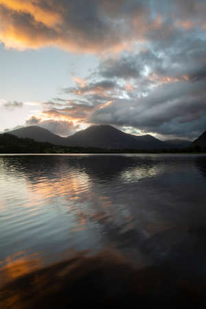 Stunning sunrise landscape image looking across Loweswater in the Lake District towards Low Fell and Grasmere with colorful sky breaking on the mountain peaks Stock Photo