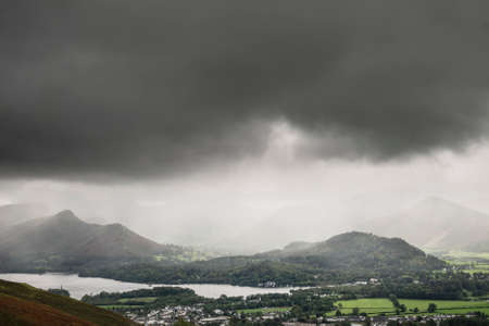 Beautiful landscape image across Derwentwater valley with falling rain drifting across the mountains onto the lush green countryside below Imagens