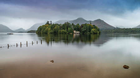 Beautiful landscape image of Derwentwater in English Lake District during late Summer morning with still water and misty mountains